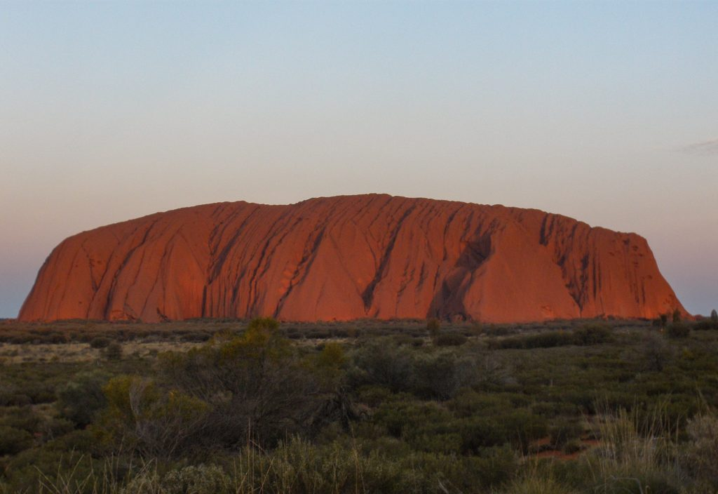 Uluru at sunrise in the heart of the red centre in the Australian Outback.